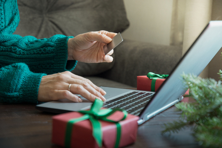 Christmas sales. Woman shopping with credit card by laptop in home interior. Xmas concept. Planing holidays.