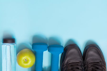 Sport and fitness equipment with sneakers, dumbbells on punchy blue. Top view with space for your text.