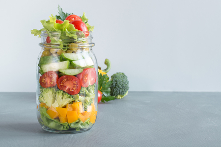 Clean eating. Vegetable healthy homemade detox colorful salad in mason jar with tomato, lettuce, broccoli. Copy space. Lunch for work. Banque d'images - 115398627