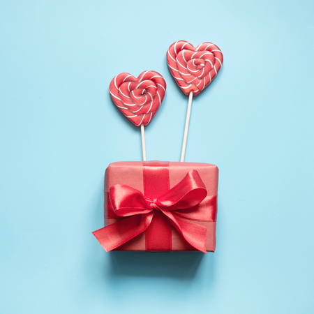 Valentines card. Two lollipops candy as heart and gift on blue background. Funny concept.