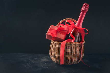 Valentines day greeting card with champagne and gift hamper on black. Space for your greetings.