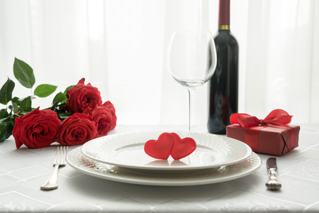 Valentines day table place setting with red roses, gift box, and wine. Space for text. Invitation for a date. Standard-Bild