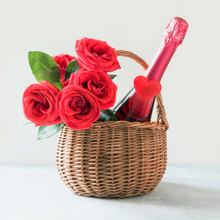 Valentine's day gift hamper, bouquet of red roses, champagne, and heart on white. Stock Photo