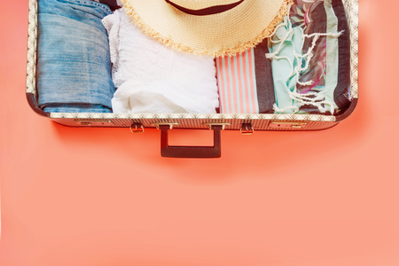 Open suitcase with female clothes for trip on living coral background. Top view with copy space. Summer concept travel.