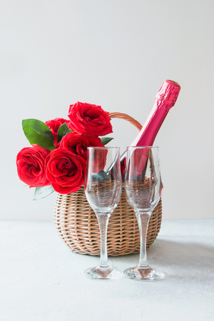 Valentine's day gift hamper, bouquet of red roses, champagne on white. Stock Photo