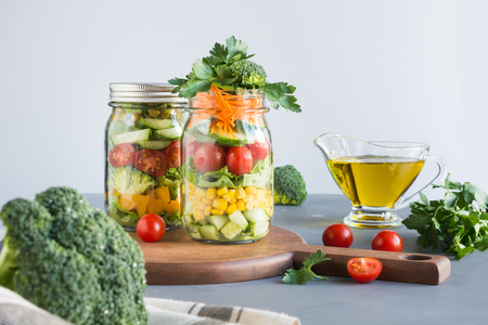 Vegetable healthy homemade detox colorful salad in mason jar with tomato, lettuce, broccoli. Copy space. Lunch for work.