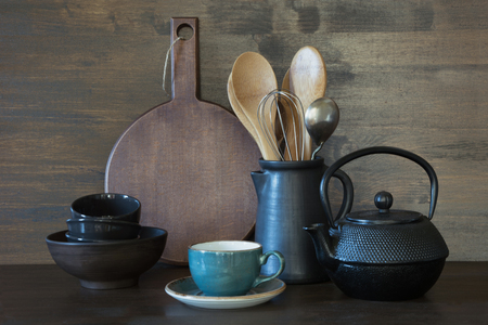 Crockery, clayware, dark utensils and other different stuff on wooden tabletop. Kitchen still life as background.