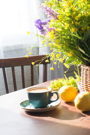 Morning with fresh cup of tea and wild flowers in basket. Stock fotó