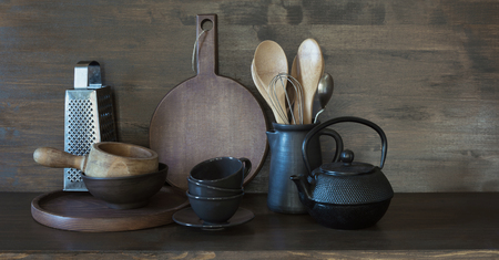 Crockery, clayware, dark utensils and other different stuff on wooden tabletop. Kitchen still life for cooking as background for design. Copy space. Imagens