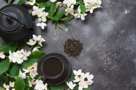 Green jasmin tea and jasmine flowers, cup of green tea on black. Top view and concept. Teatime. Copy space.