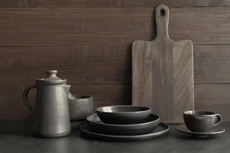 Crockery, clayware, dark utensils and other different stuff on dark wooden tabletop. Kitchen still life for cooking as background for design. Copy space. Imagens