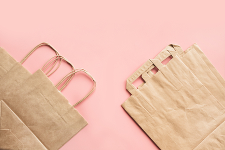 Paper bags for zero waste shopping on pink background. Space for text.
