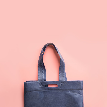 Blue textile bag for zero waste shopping on pink background. Space for text.