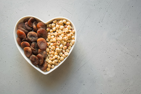 Dried organic apricots and hazelnut in plate as shape of heart on grey concrete background. Space for text.