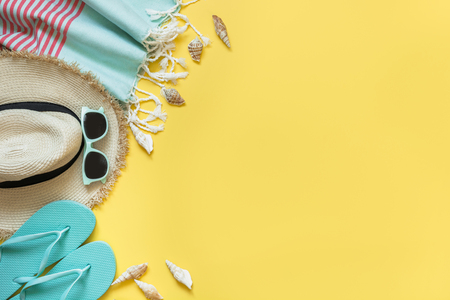 Outfit for beach and tropical vacations, straw sunhat,towel, sun glasses on yellow with space for text. Summer concept.