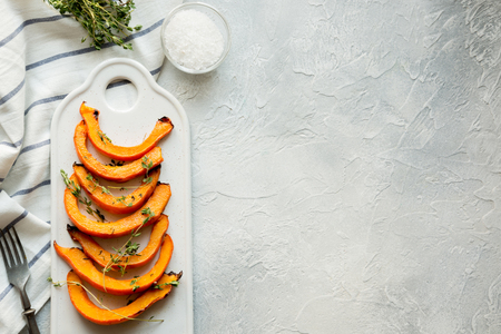 Zucca arrostita e grigliata con aggiunta di timo aromatico e sale su bianco. Cibo vegano sano. Vedi rom sopra.
