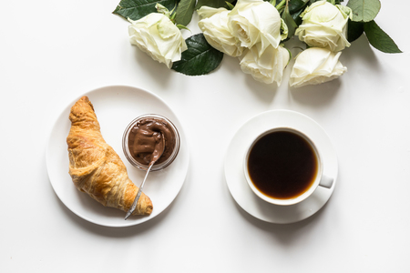 Cup of coffee and freshly baked croissants on white background. Top view. Copy space. Little female pleasure.