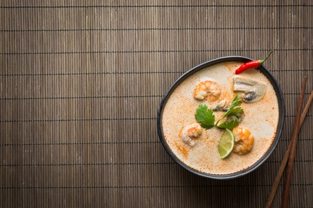 Tom yam kung spicy thai soup with shrimp, seafood, coconut milk, chili pepper on mat. Space for text. Stock Photo