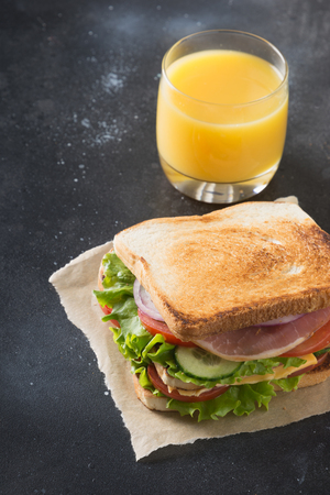 Sandwich with bacon,tomato, onion, salad on black. Close up.