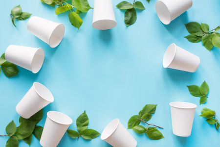 Border of white disposable cup and green leaves on blue background. Save the planet. Zero waste. Space for text and top view.