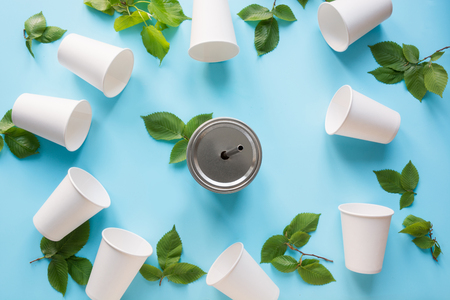 Border of white disposable cup and green leaves on blue background. Save the planet. Zero waste life. Space for text and top view.