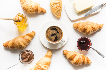Freshly baked croissants and cup of coffee on white. French breakfast. View from above. Banco de Imagens