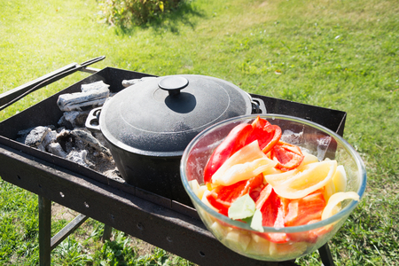 Process cooking shurpa soup in a large cast-iron cauldron outdoor. Summer food for hike. Turkish cuisine.