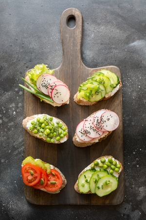 Different vegan sandwiches with vegetables, radish, celery, tomato, rye bread on black. Top vew. Appetizer for party. Flat lay. Stock Photo