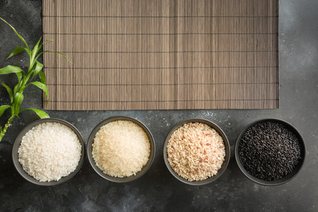 Different varieties of rice in bowls. Top view. Black background. Space for text. View from above.
