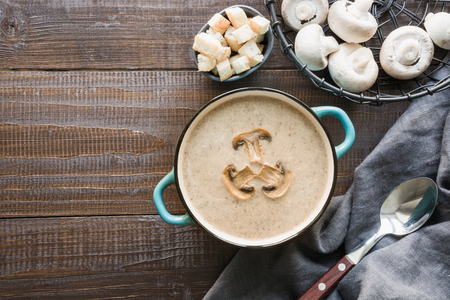Delicious mushroom champignon cream soup on dark wooden board. Top view. Space for text. Horizontal orientation
