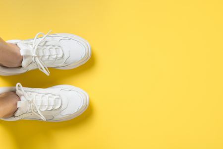 Pair of white female sneakers on yellow. Flat lay, top view minimal background. Magazine concept. 免版税图像