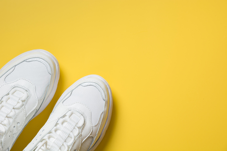 Pair of white female sneakers on yellow. Flat lay, top view minimal background. Magazine concept. Imagens