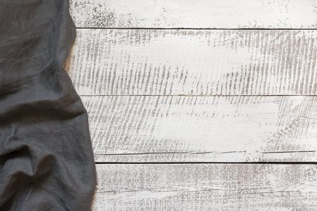 Rustic gray linen napkin on wooden board with space for your menu or recipe. Menu card for restaurants. Top view.