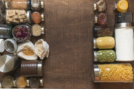 Raw grains, cereals and pasta in glass jars on wooden tabletop. Healthy cooking, clean eating. Space for text. Storage and save. Zero waste concept. View from above.