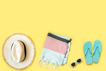 Beach female accessories, straw beach hat, towel, sunglasses on yellow. Top view. Space for text. Summer tropical vacation. Stockfoto