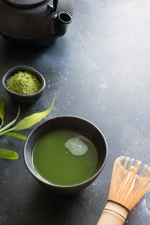 Organic green matcha tea in bowl on black table. Close up. Space for text.