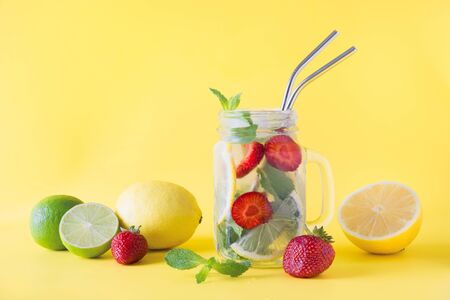 Detox water, lemonade or mojito with lemon, lime, strawberry in mason jar on yellow. Summer healthy freshness drink. Space for text. Horizontal orientation. Close up.