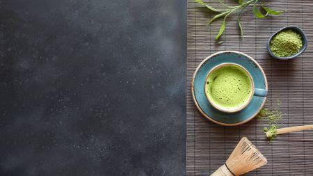 Martwa natura z japońską zieloną herbatą matcha z akcesoriami na czarnym stole. Widok z góry. Miejsce na tekst.