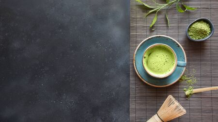 Still life with Japanese matcha green tea with accessories on black table. View from above. Space for text.