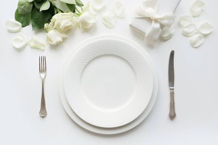 White table setting with bouquet rose, gift, dishware, silverware on holiday white table. Top view. Romantic and wedding anniversary.