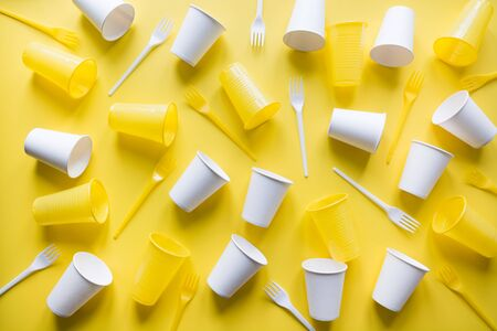 Disposable picnic utensils for recycling on yellow. Environment eco friendly discarded plastic garbage for recycle concept.Top view. Flat lay. Pattern. Stock Photo