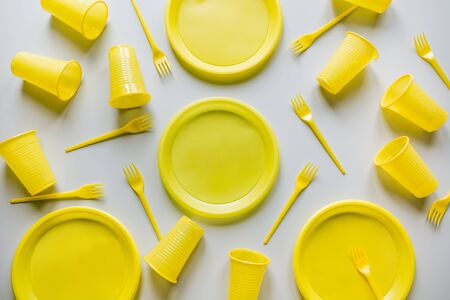 Single use yellow picnic utensils on grey. Environment, eco friendly, discarded, plastic garbage for recycle concept.Top view. Flat lay. Pattern. Archivio Fotografico