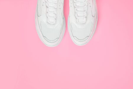 Pair of white female trendy sneakers on pink. Flat lay, top view minimal pink background. Space for text.
