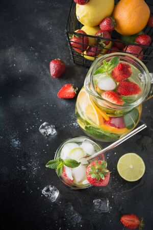 Detox water or mojito with lime, orange, strawberry in rocks glass. Summer healthy freshness drink. Vertical orientation. Dark wooden background. Close up. Space for text. Top view.