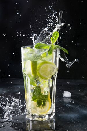 Splash of mojito cocktail or lemonade with lime and mint in rocks glass on black. Close up. Summer refreshing drink.