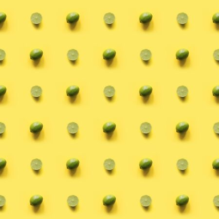 Seamleas limes pattern on punchy yellow background. Creative food concept. Flat lay. Top view.
