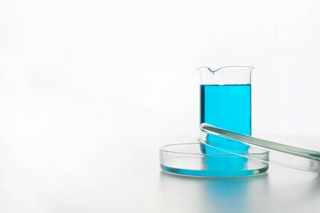 Chemistry glassware with blue liquid for science research and experiment. Space for text.