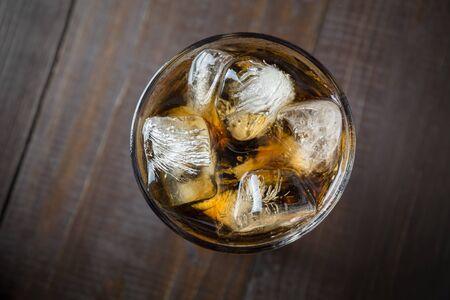 Cola mit Eiswürfeln auf dunklem Holzbrett. Von oben betrachten. Nahansicht. Sommerfest. Horizontale Ausrichtung. Standard-Bild