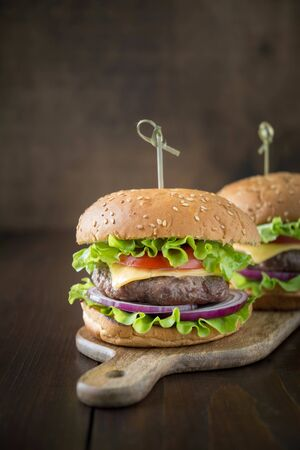 Fresh two beef burgers with vegetables with cola on wooden board. Summer party. Close up. Vertical orientation.