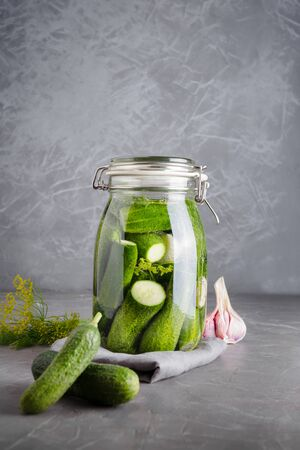 Pickling and fermentation cucumber in glass jar with dill and garlic on dark grey concrete tabletop. Close up. Reklamní fotografie - 127587108